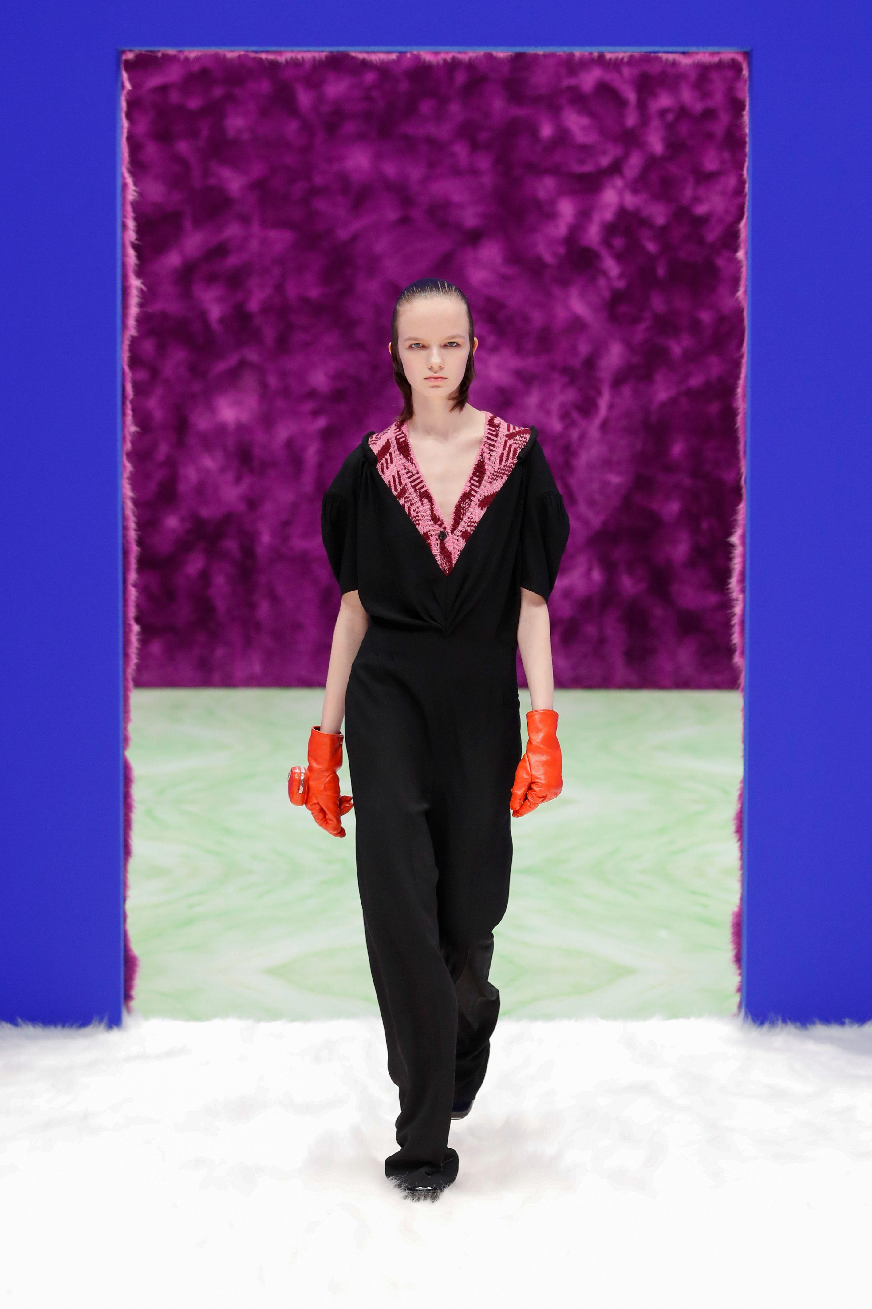 Una elegante monoprenda negra superpuesta con sweater tejido bicolor en rosa y rojo, otro de los looks protagonista de Prada