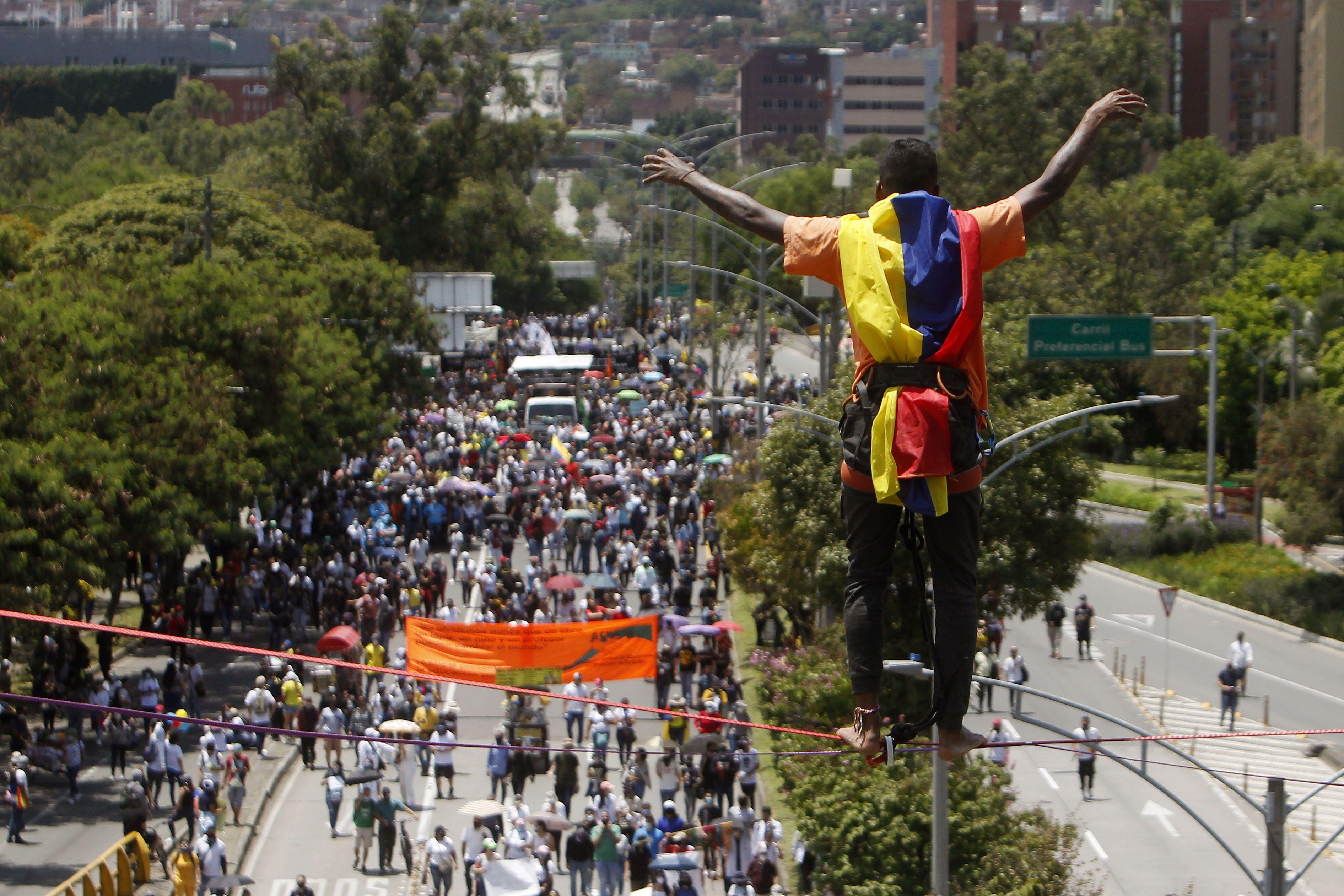 Un hombre realiza acrobacias frente a cientos de personas que marchan durante una nueva jornada de protestas en el marco del Paro Nacional, en Medellín (Colombia). EFE/ Luis Eduardo Noriega A.