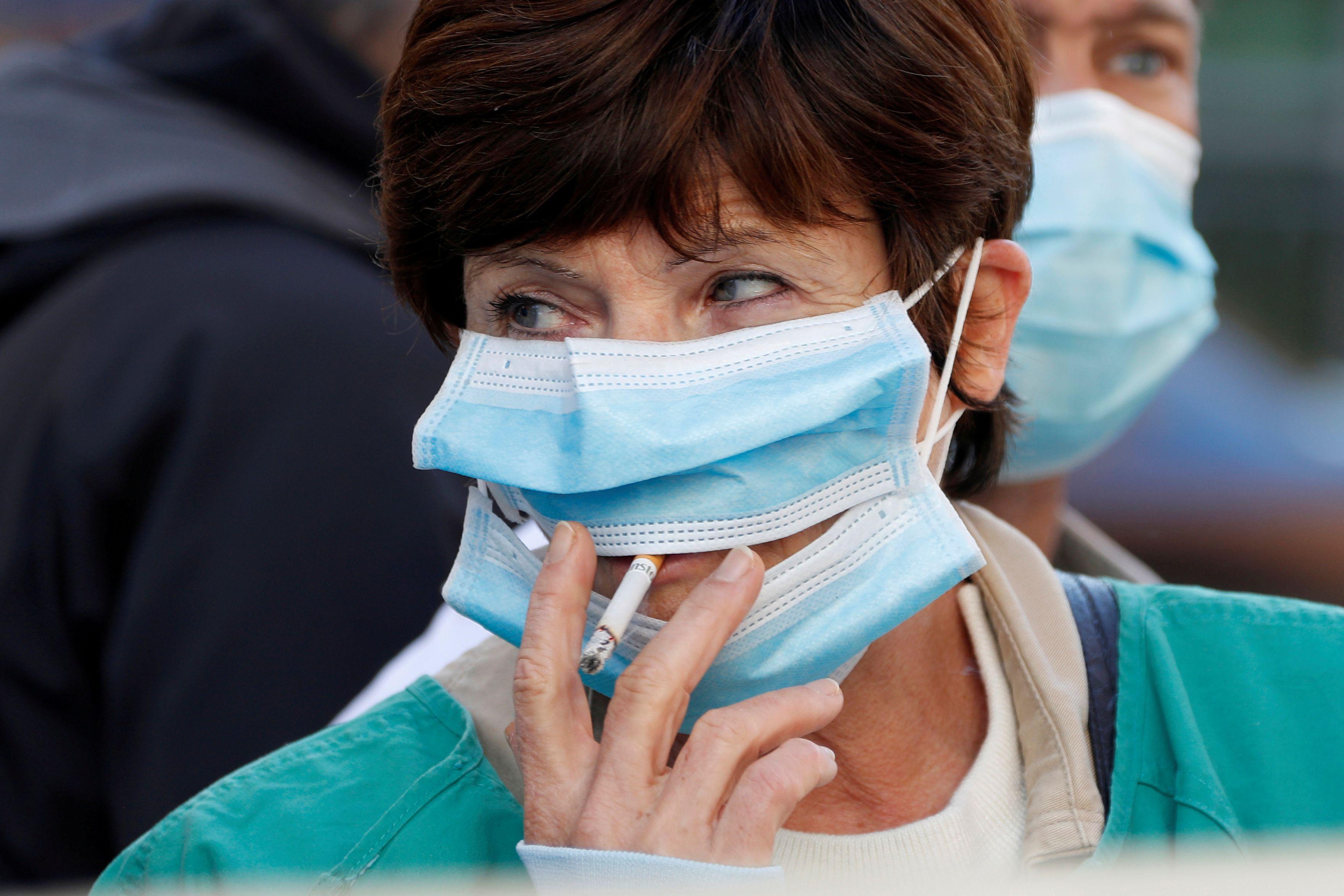 Si una persona se retira el barbijo en un patio o terraza, se pone a fumar tabaco, y permanece con otras personas a menos de dos menos, sí aumenta su riesgo de contraer el coronavirus y de contagiar al otro (Reuters)