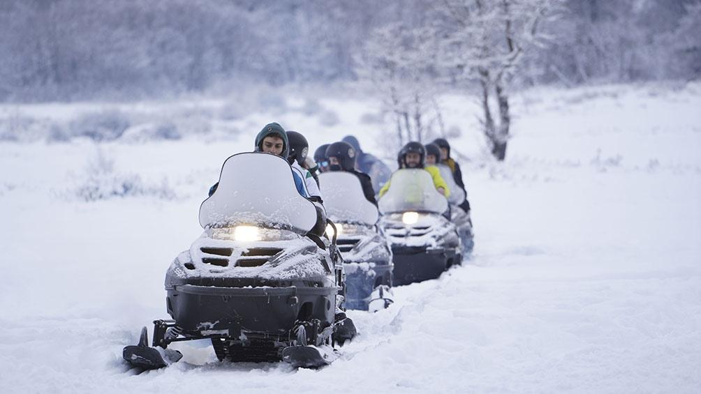 Una opción es andar en moto de nieve para recorrer un circuito entre el bosque nevado.