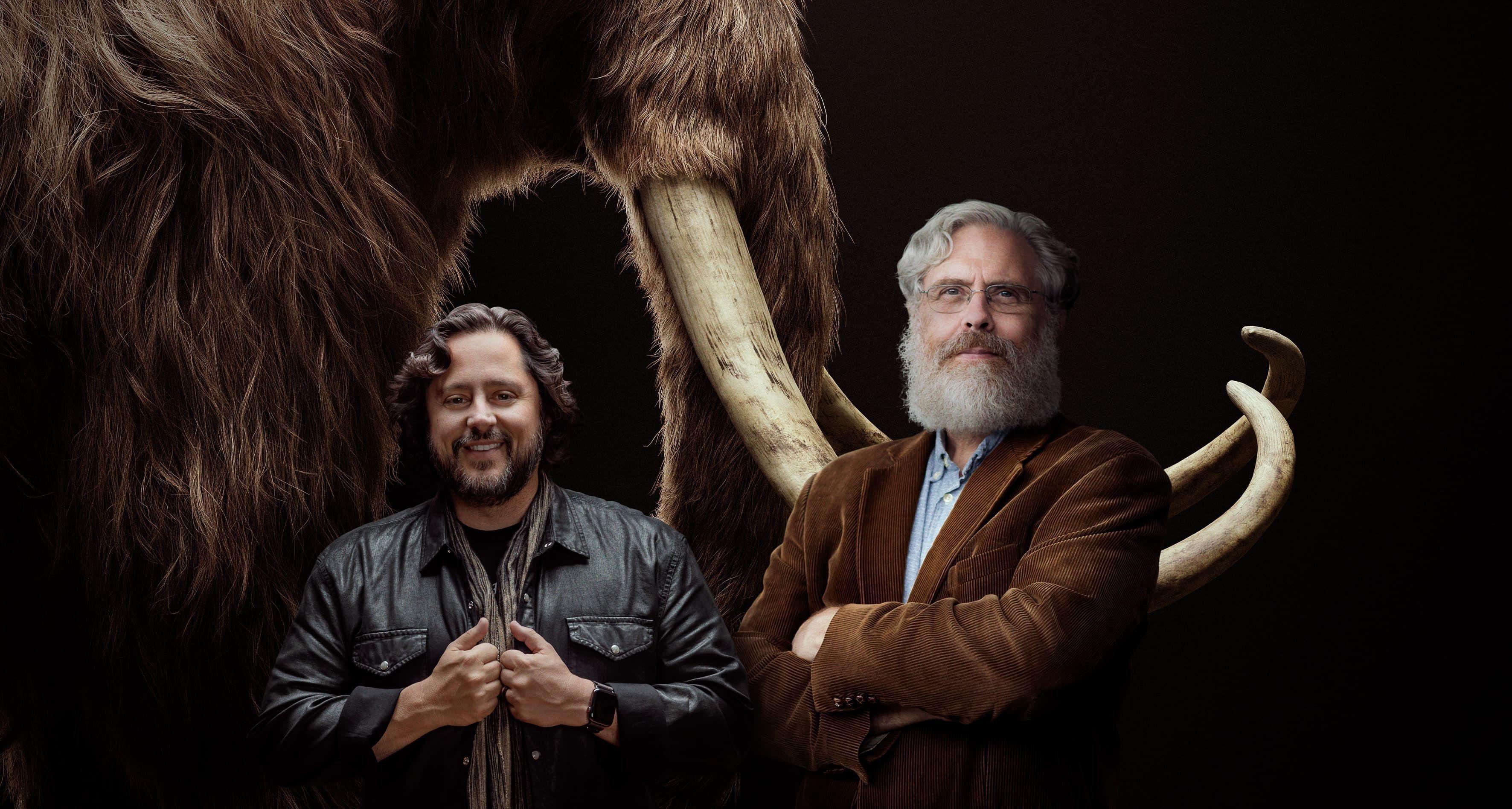 Los cofundadores de Colossal, los empresarios y científicos Ben Lamm y George Church, mientras posan frente a la imagen de un mamut (EFE/Colossal)