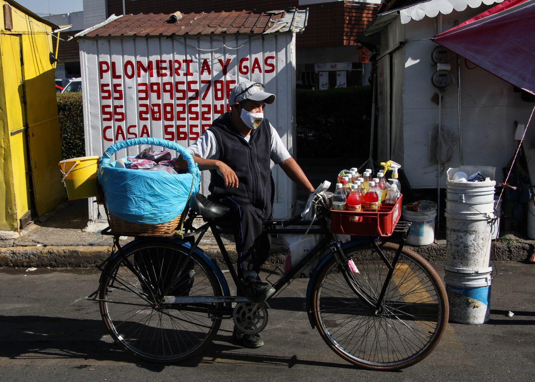 Vendedor de tacos de canasta en bicicleta, se mantiene a la espera de clientes frente a un local de plomeria y gas, esto sobre Avenida Miguel Ángel de Quevedo.FOTO: ROGELIO MORALES /CUARTOSCURO.COM