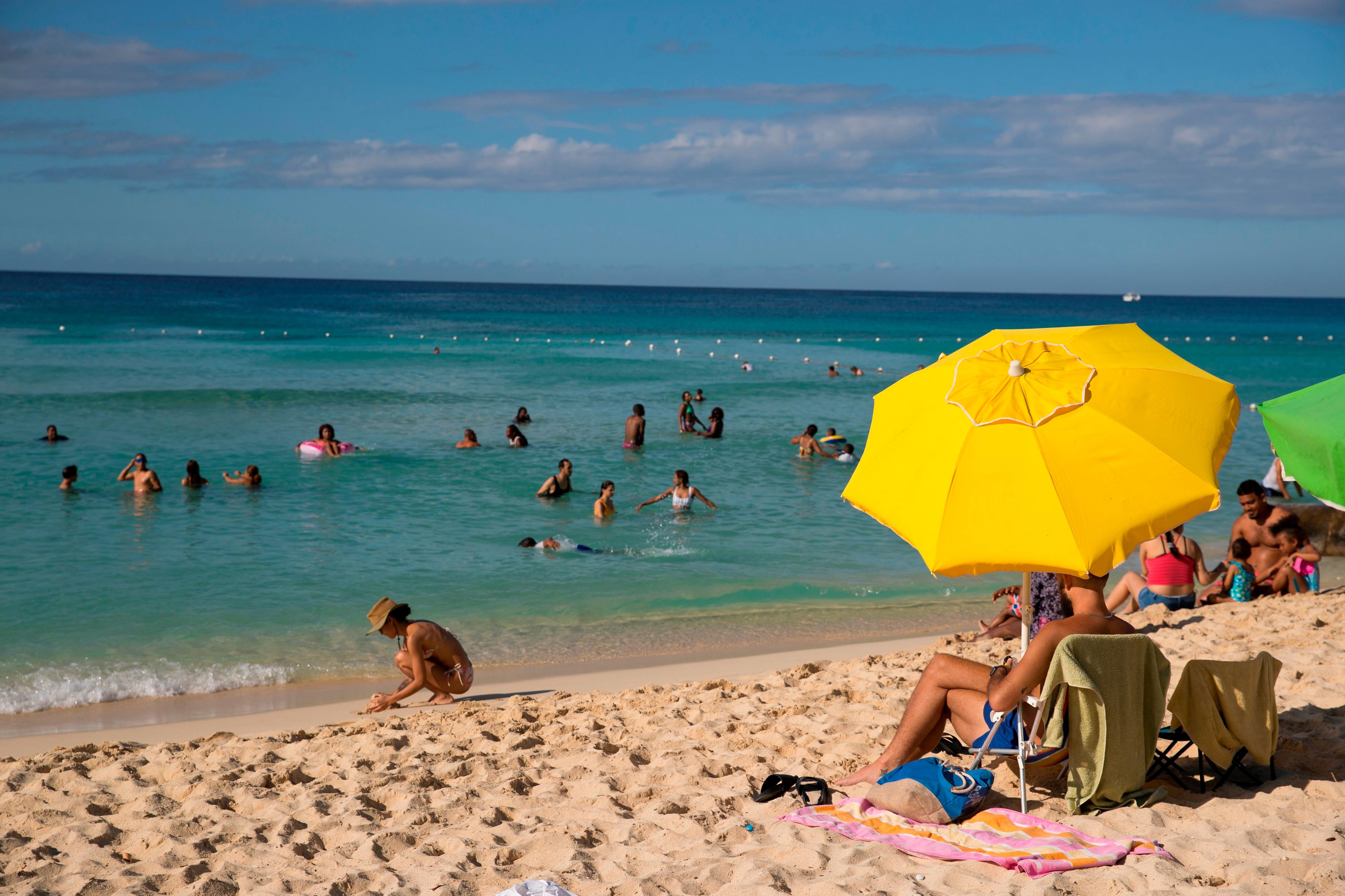 Fotografía de archivo de grupos de personas mientras se encuentran en la playa en Bayahibe (R.Dominicana). EFE/ Orlando Barría